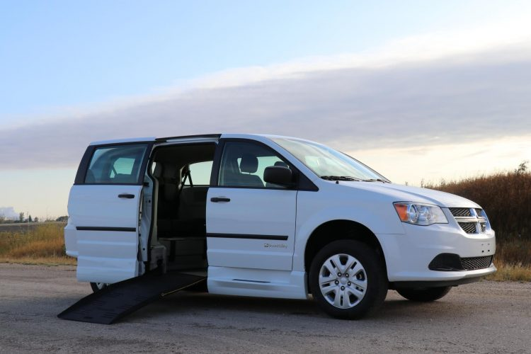side view of braunability commercial e3 side entry dodge minivan with ramp deployed