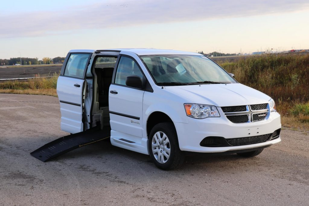 3/4 front view of braunability commercial e3 side entry dodge minivan with ramp deployed